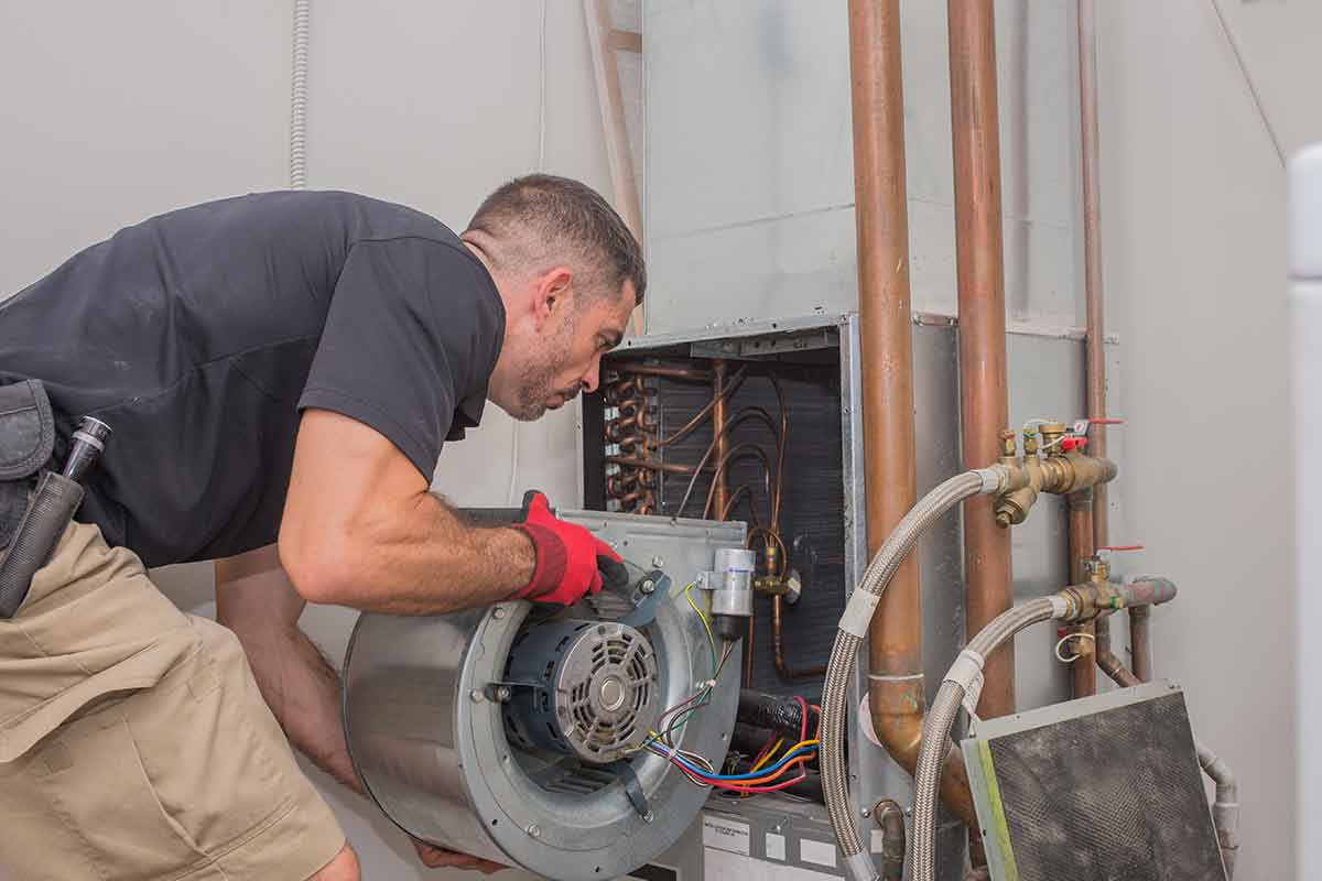 HVAC technician removing blower unit