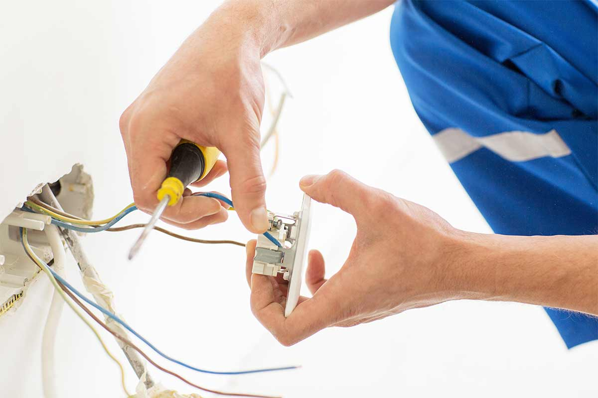 Hands holding an electrical outlet to repair and reinstall