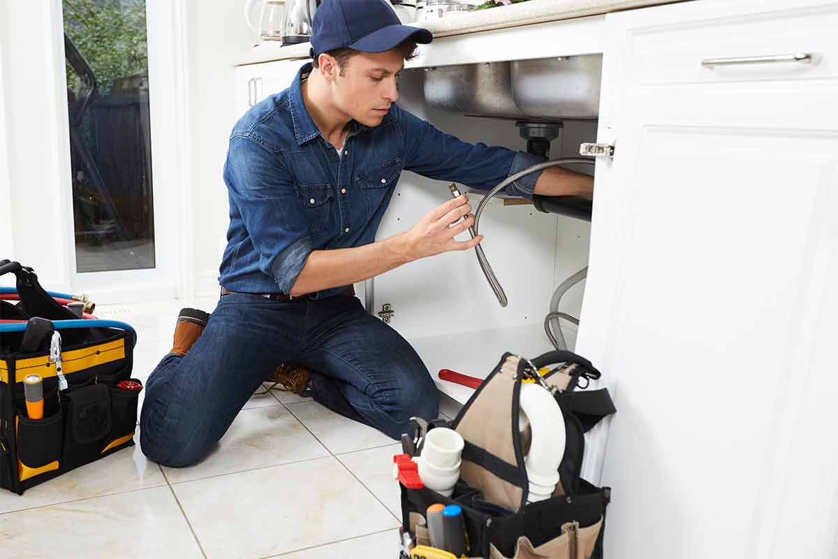 Male plumber wearing blue uniform and kneeling in front of open kitchen sink counter to fix plumbing underneath