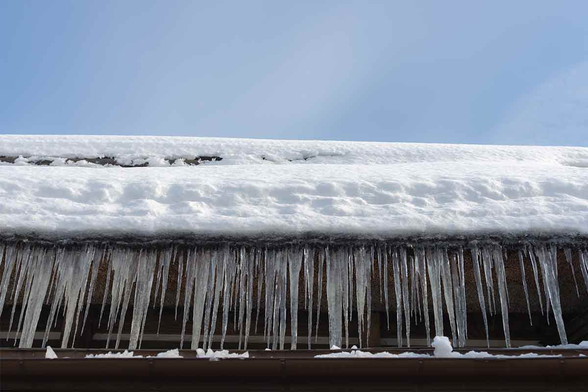 Edge of a roof with significant ice dams and icicles