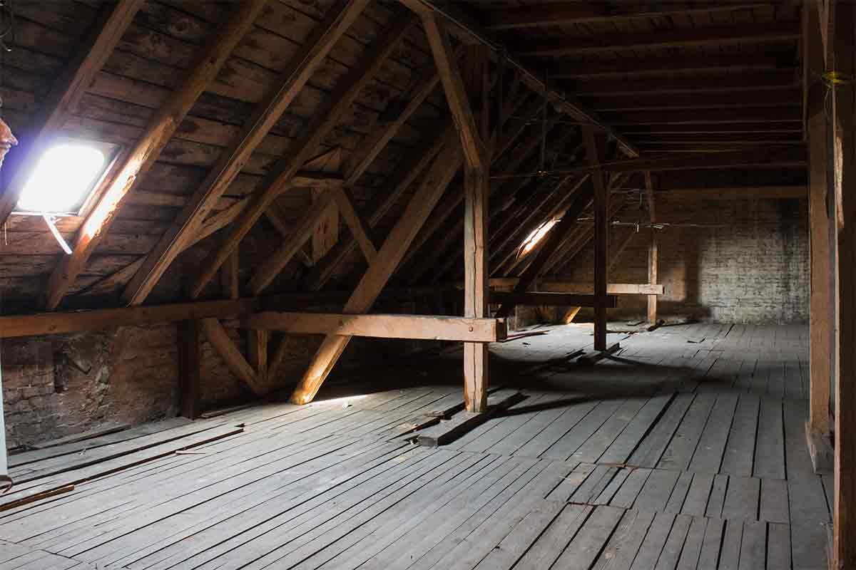 Empty, unfinished attic with wood floor and exposed wood beams