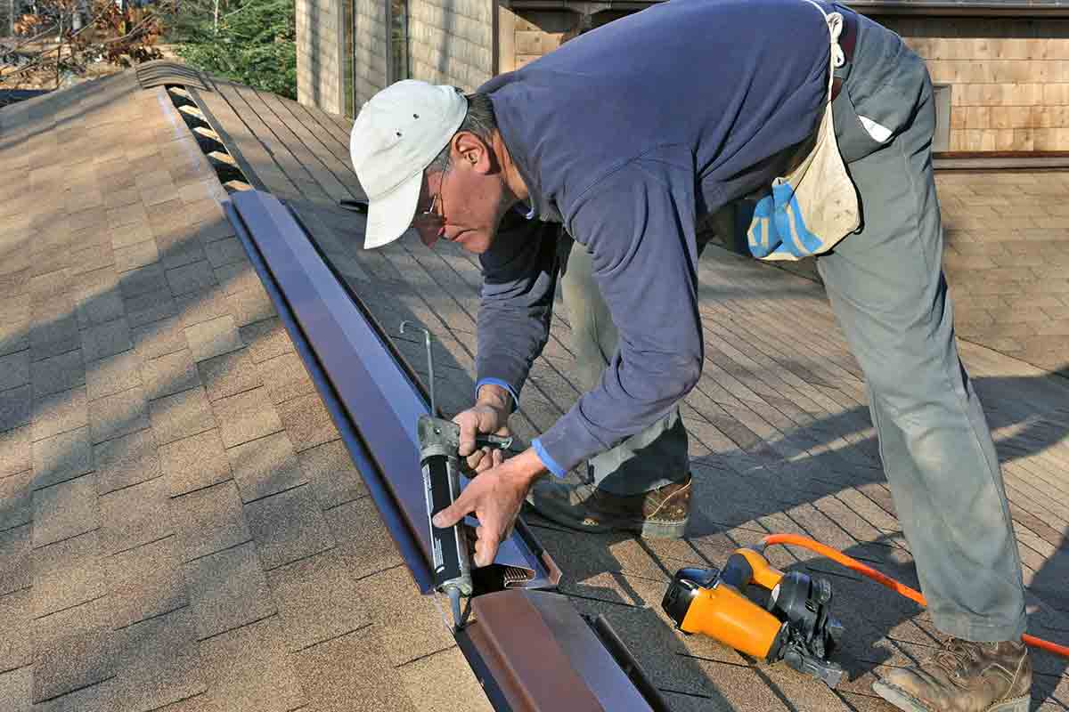 Roofer installing ridge vents on a roof