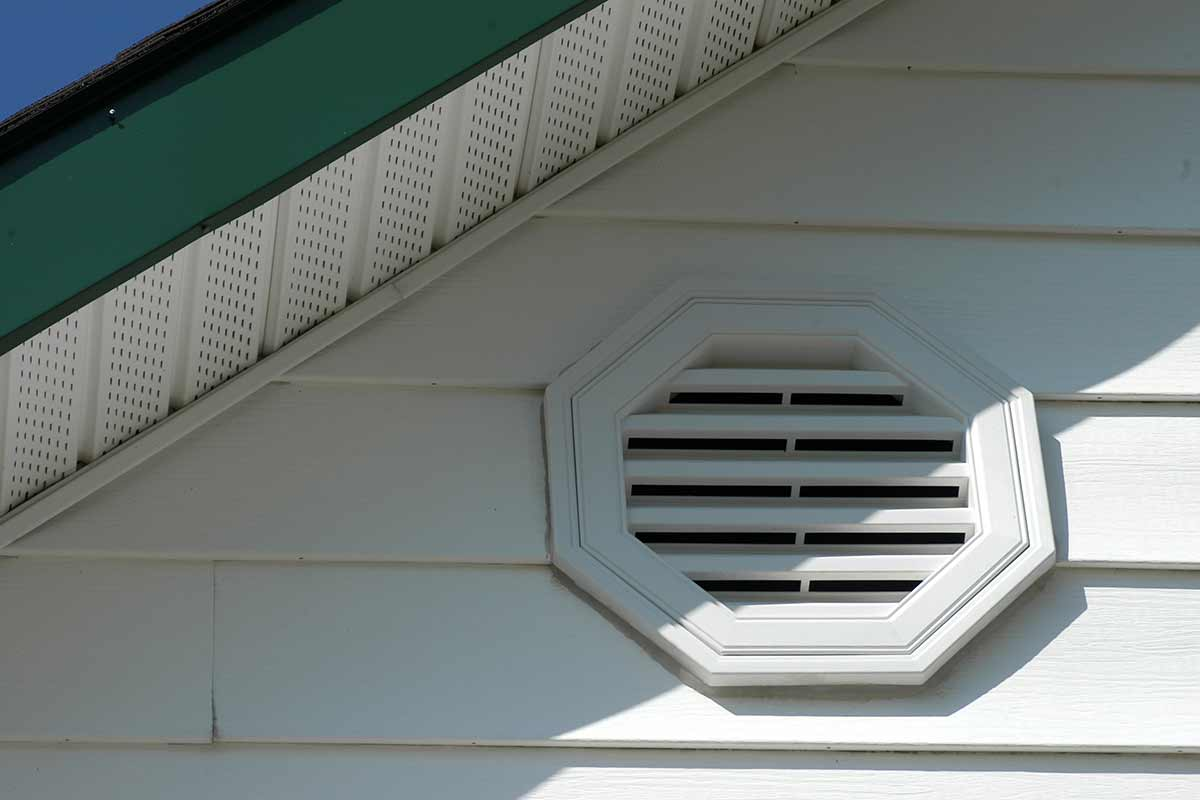 Close-up of a white house with a gable vent and soffit vents