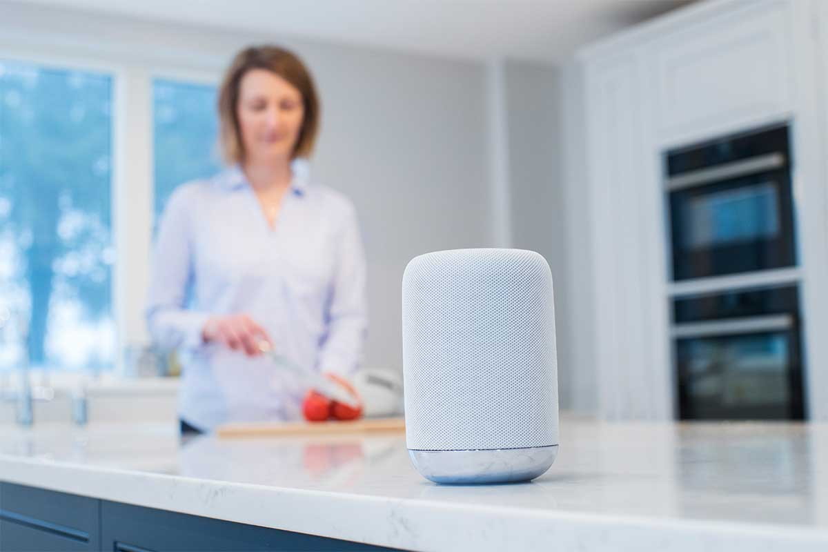 Close-up of a smart speaker with a woman cooking in the background