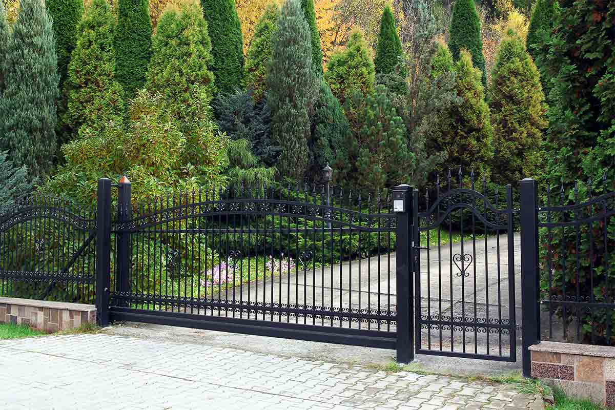 Black wrought iron fence and rolling gate