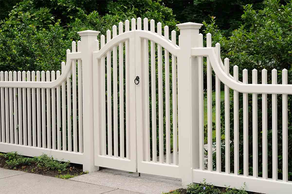 White picket fence with a curved-top gate