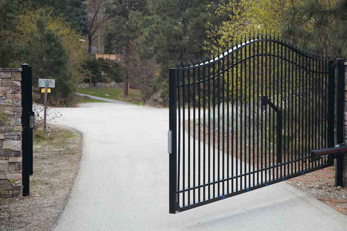 Black metal automated gate opening to a driveway
