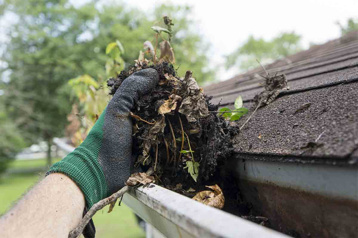 hand cleaning dirt nd debris out of gutters