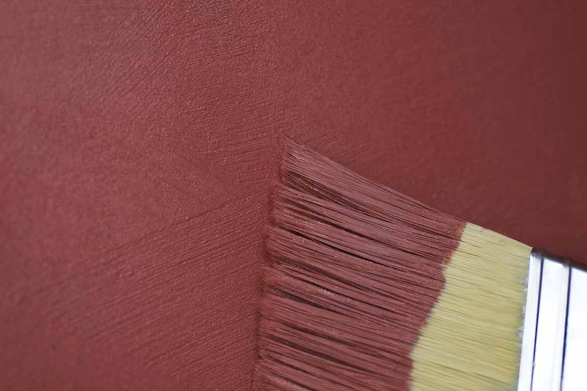Close-up image of paint brush and brushstrokes in red paint