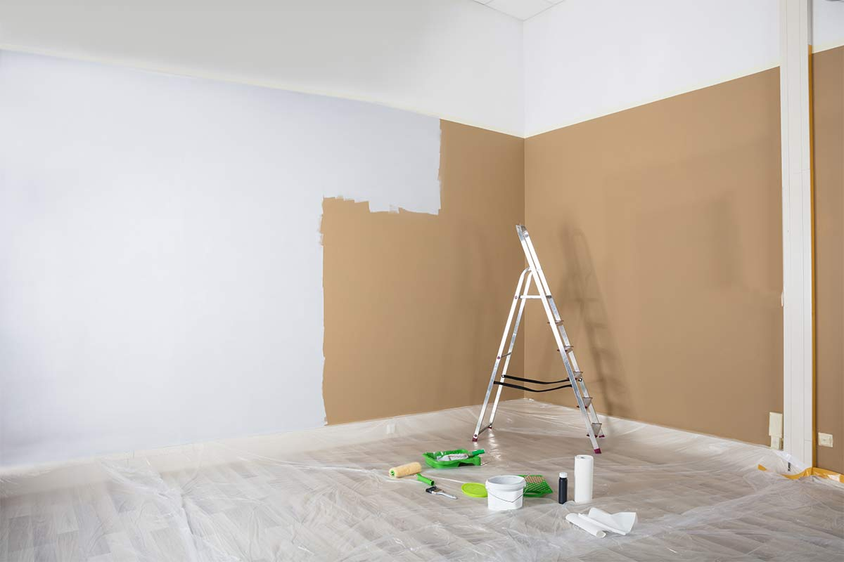 Room half painted white with ladder and painting tools