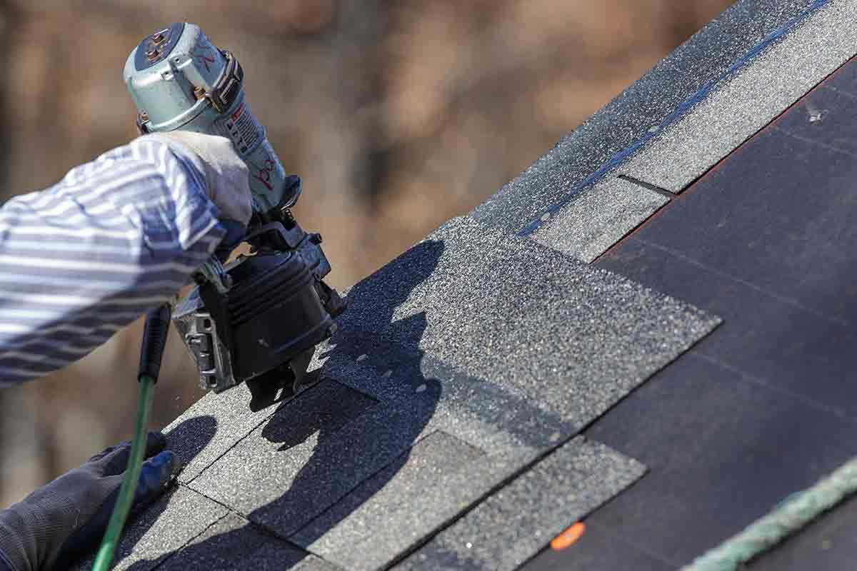 nail gun attaching shingles on roof