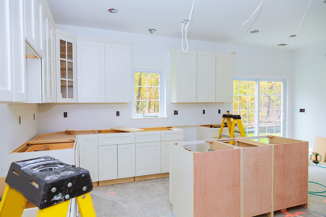 white kitchen cabinets in various stages of installation