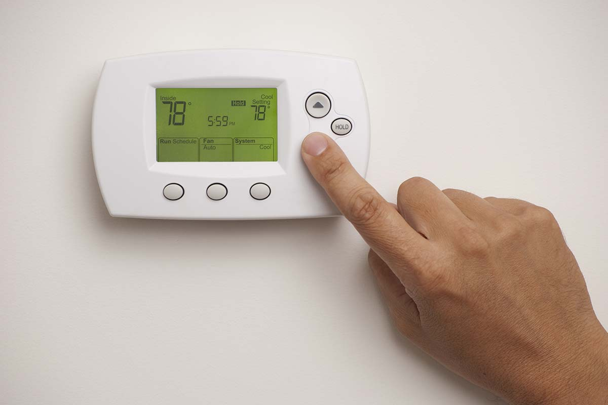person lowering temperature on digital thermostat