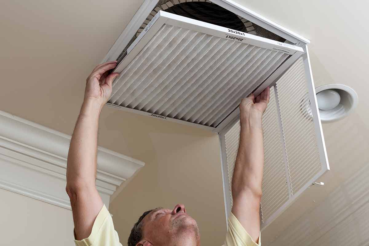 man changing air filter for HVAC system
