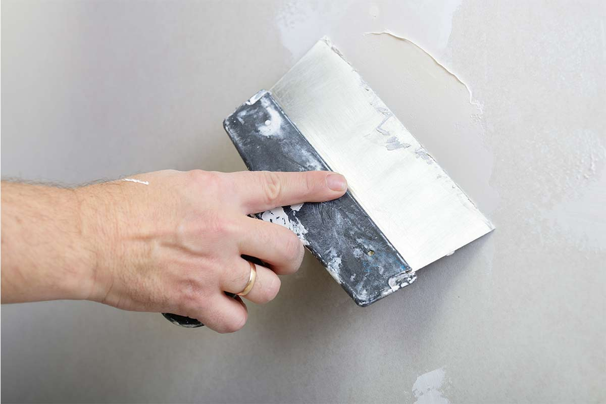hand-using-putty-knife-and-drywall-compound-to-repair-drywall
