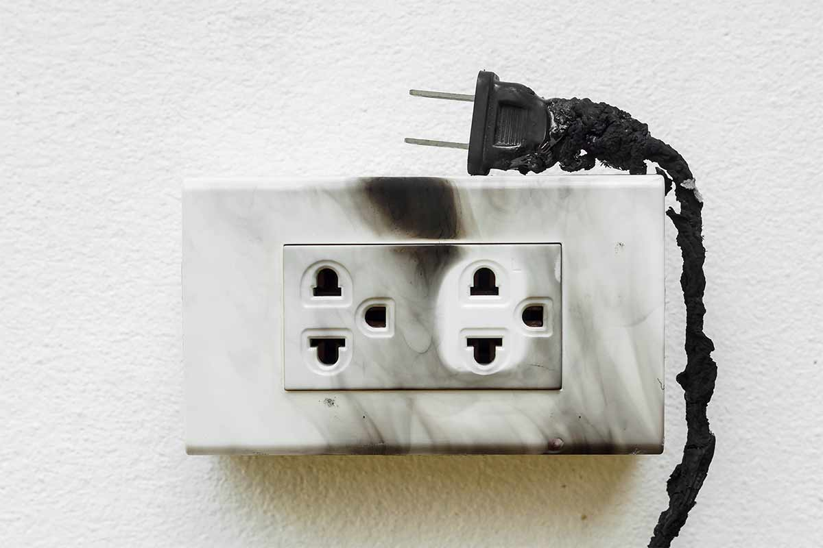 burnt-discolored-outlet-with-charred-power-cord