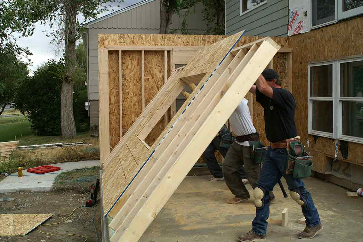 construction workers installing wall frame