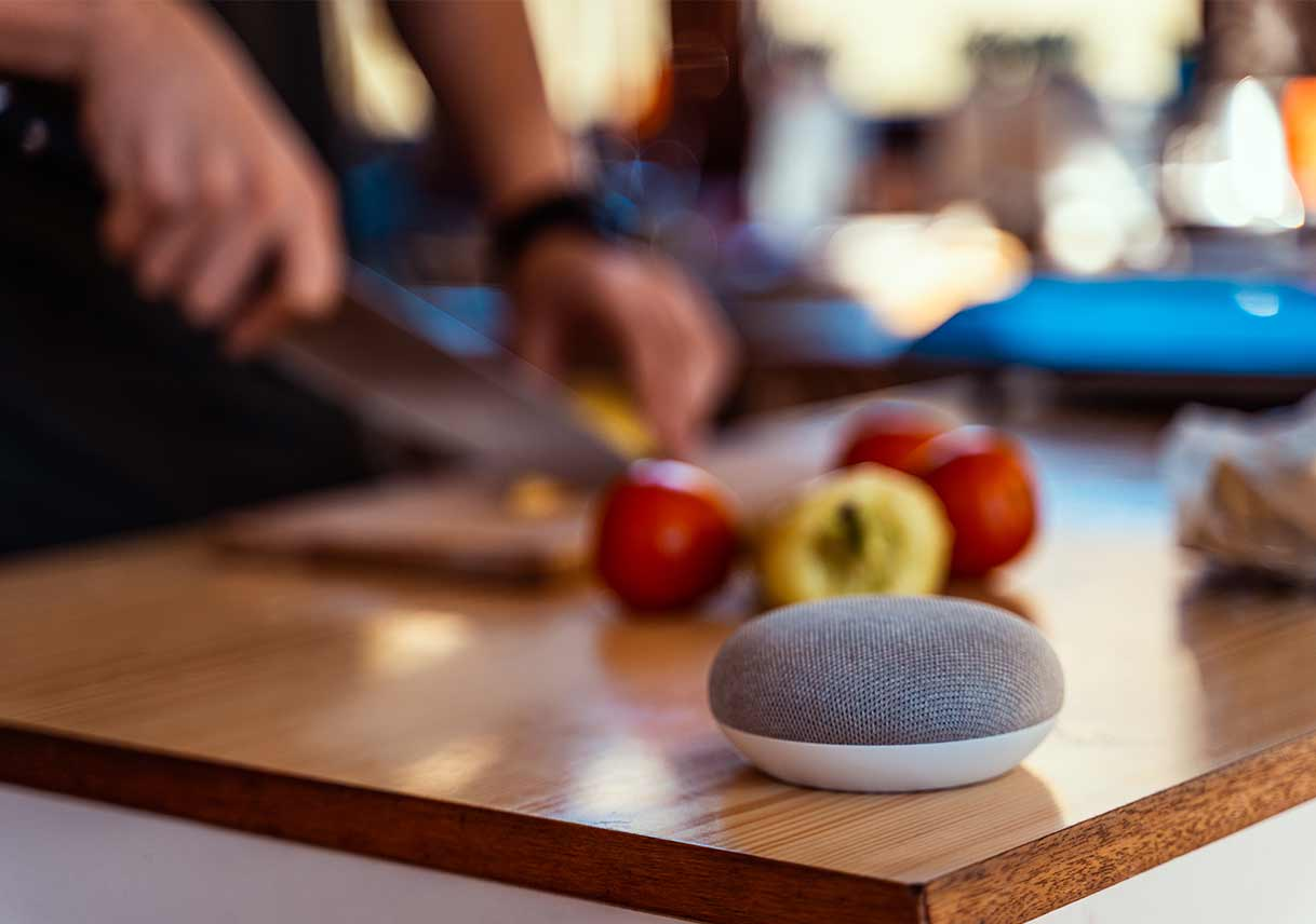 Smart-speaker-on-kitchen-counter-with-man-chopping-vegetables-in-background