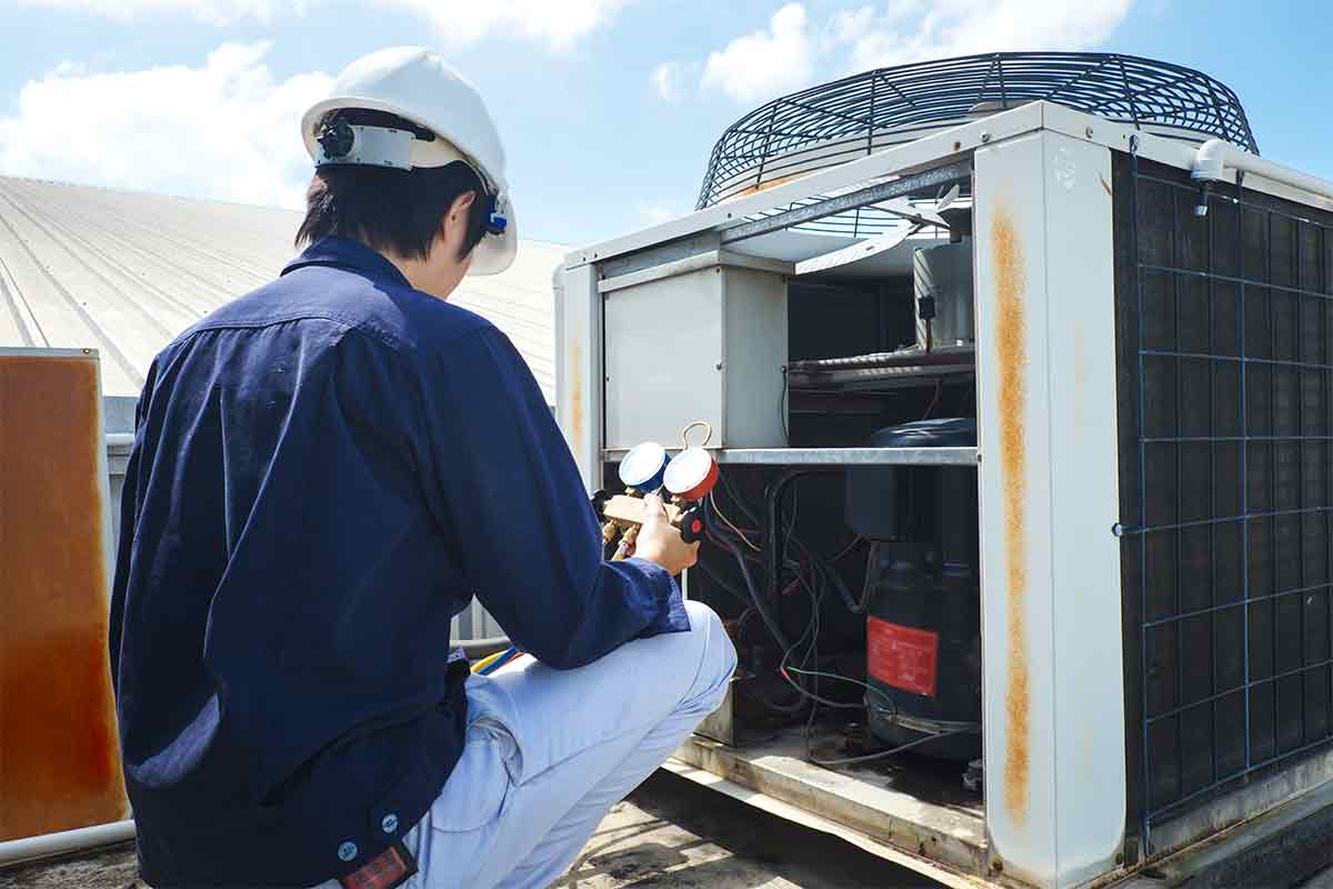 HVAC technician repairs air conditioner unit