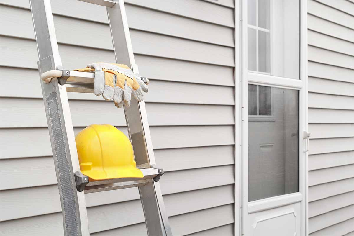 Metal ladder with work gloves and yellow hard hat leaning against white vinyl siding
