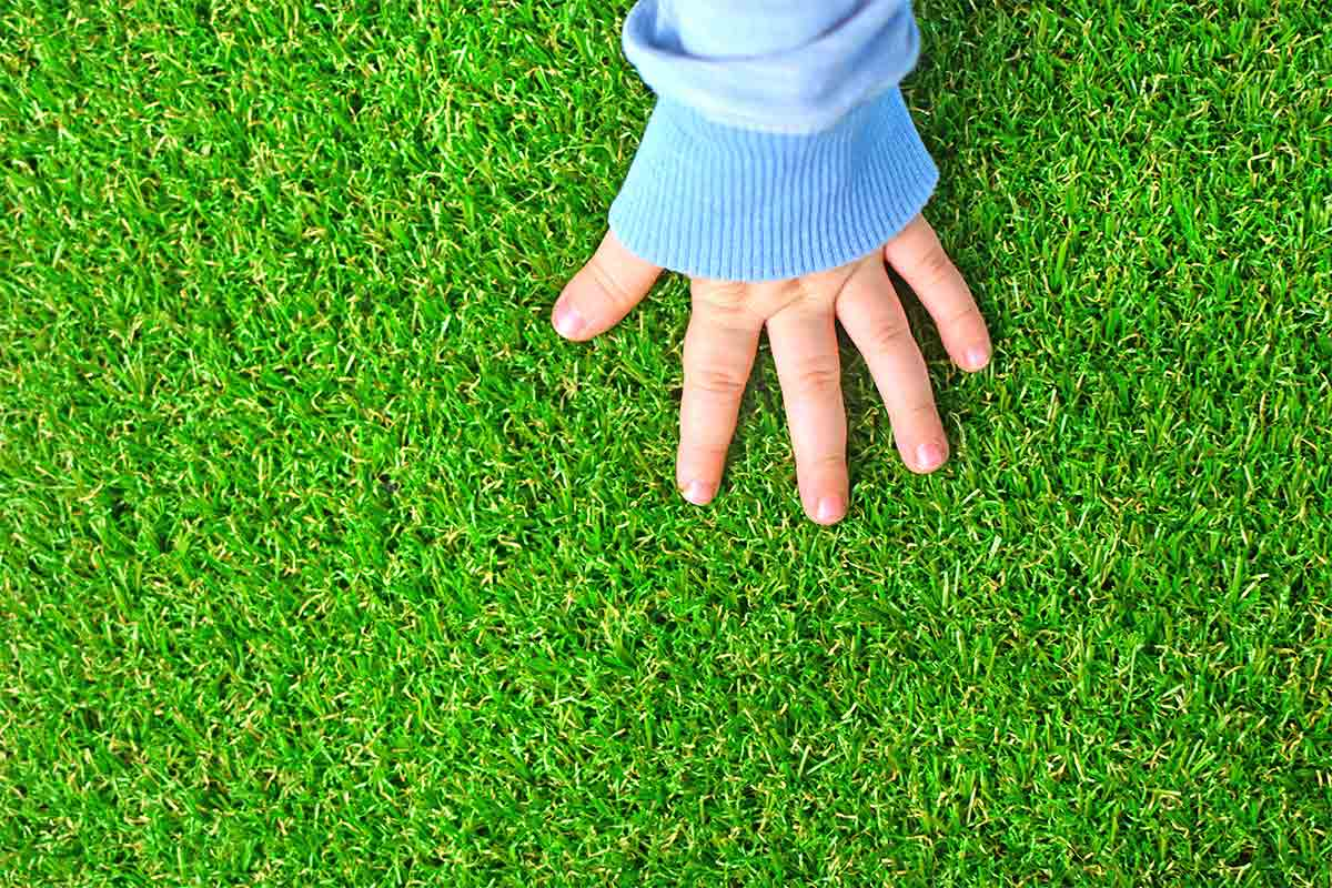 child-touching-synthetic-grass-or-turf