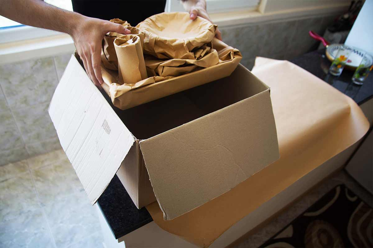 man packing dishware wrapped in moving paper
