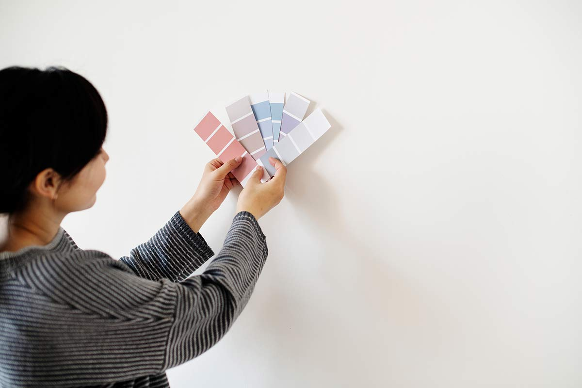 woman-comparing-paint-samples-in-front-of-wall