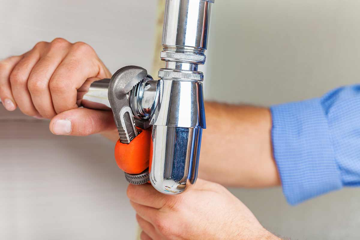 Plumber using a wrench to tighten part of a pipe fixture