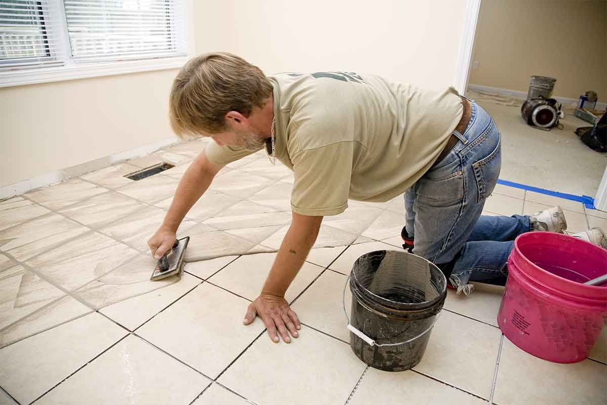 tile installer laying grout