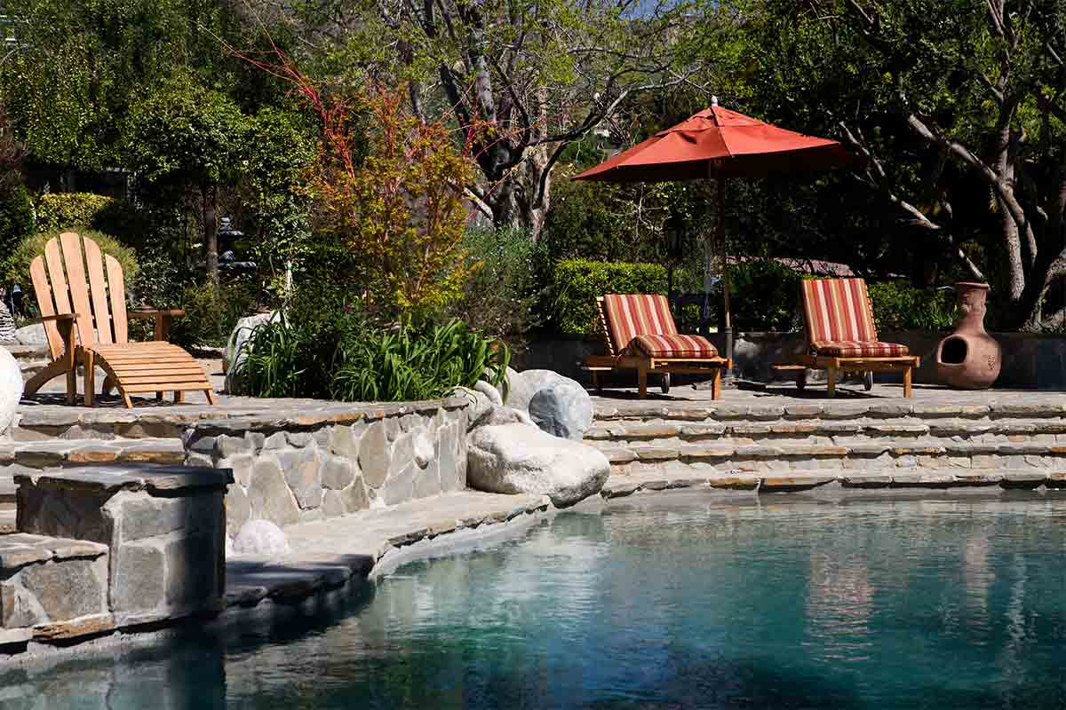 saltwater pool with rock surround and patio furniture