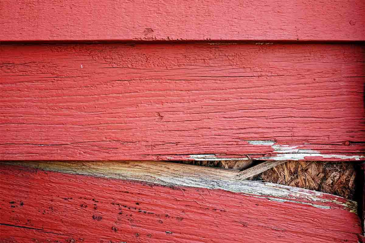 red clapboard siding falling apart due to dry rot