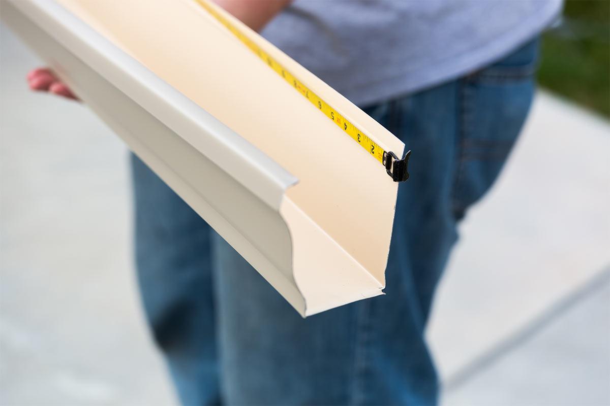 gutter installer measuring aluminum gutter