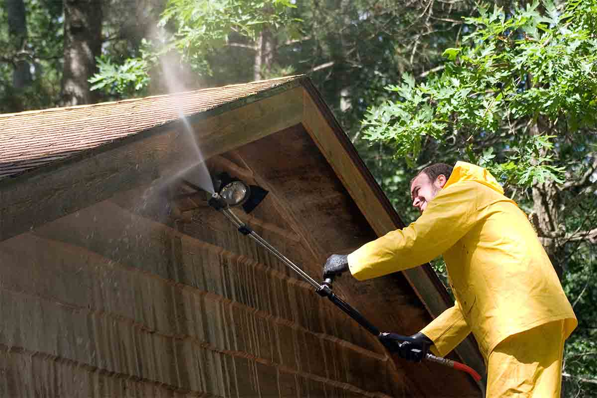 man using pressure washer to clean wood siding