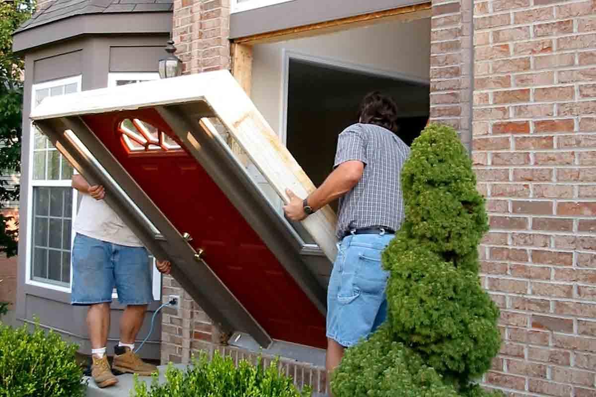 Two contractors installing a prehung front entry door