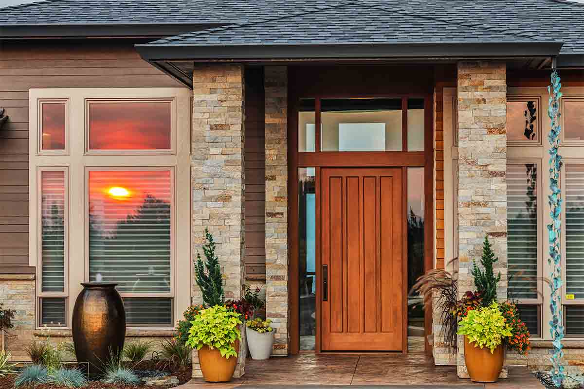 Wooden front entry door on a modern-style house with sunset reflected in front window of house
