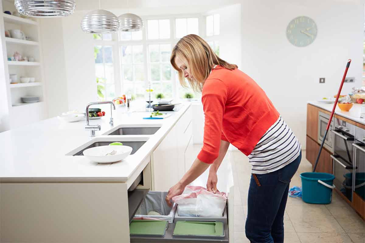 woman emptying trash in kitchen