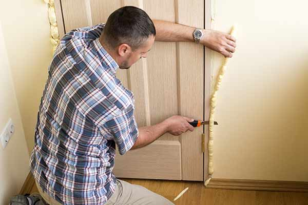 man cuts off excess foam from door