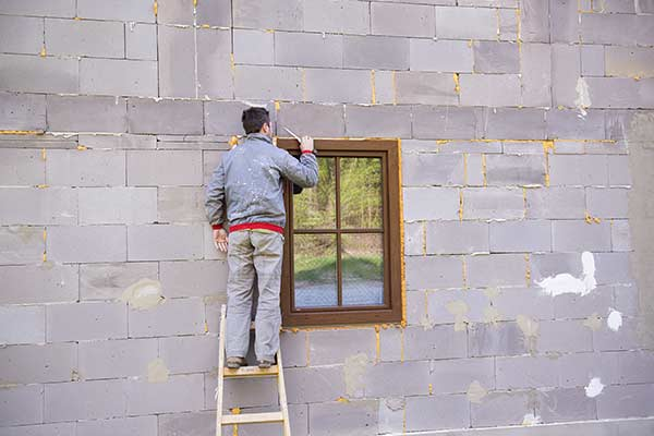 man resealing window from outside