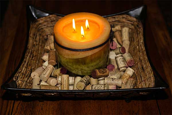 centerpiece with candle resting on used wine corks in wicker tray