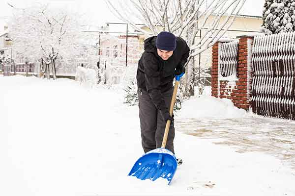 man shoveling sidewalk in front of house