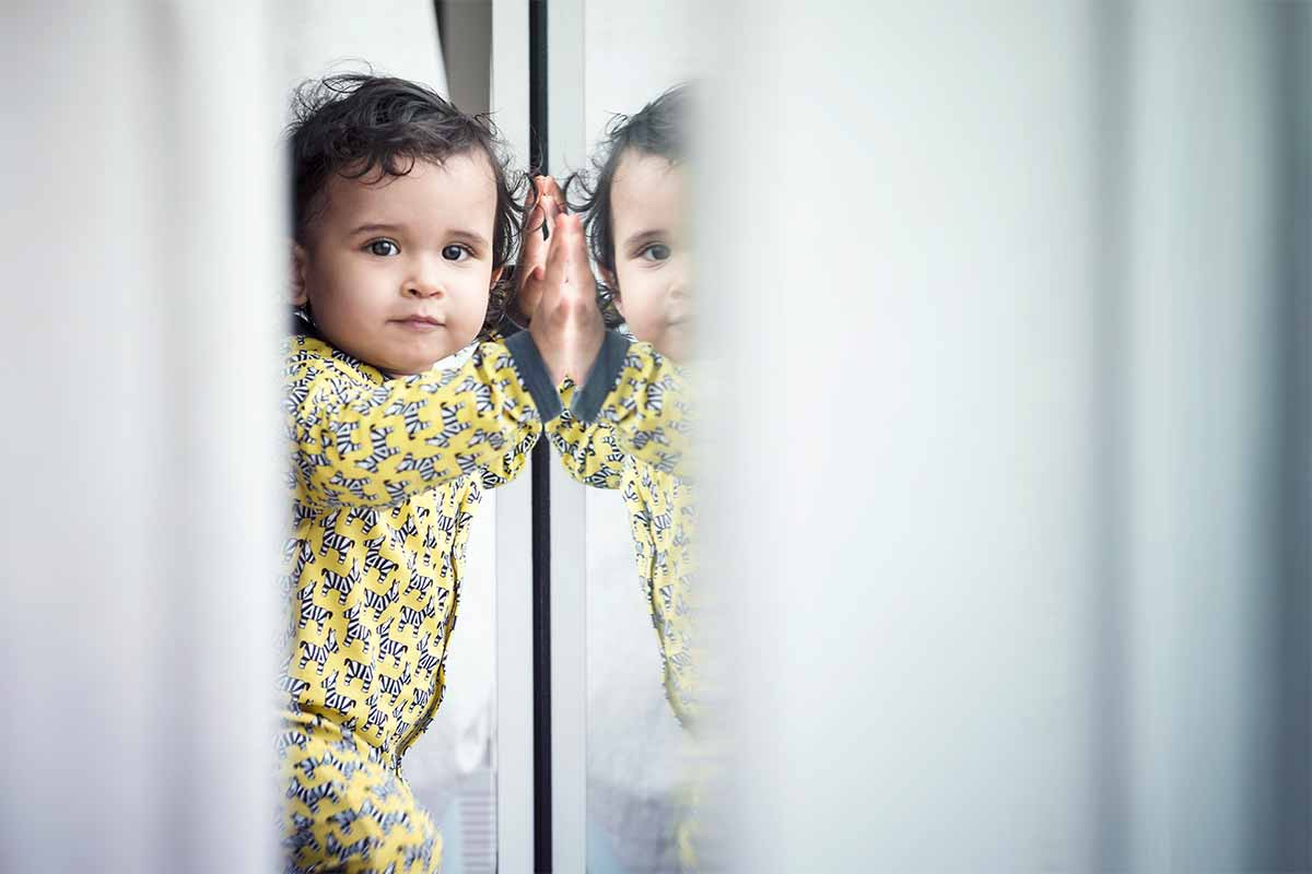 baby leaning against glass