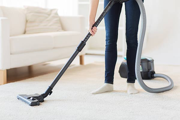 woman cleaning carpet in living room