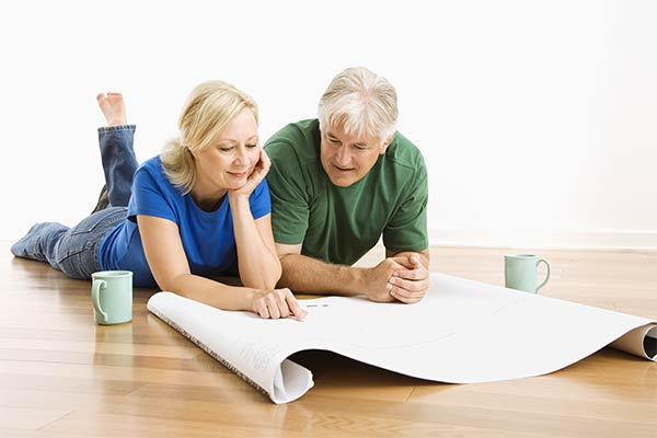 couple lying on floor looking at blueprints