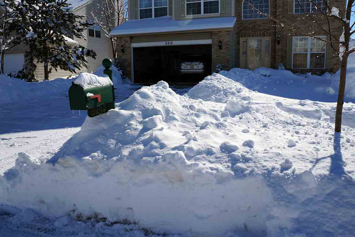 snow piled high in front yard of house