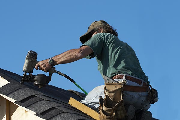 roofer putting down new shingles
