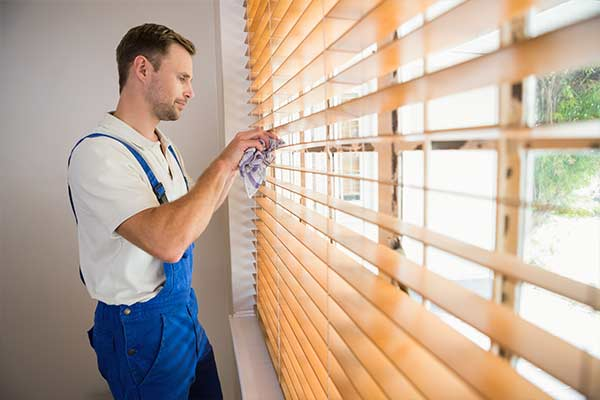 man cleaning window blinds with a rag