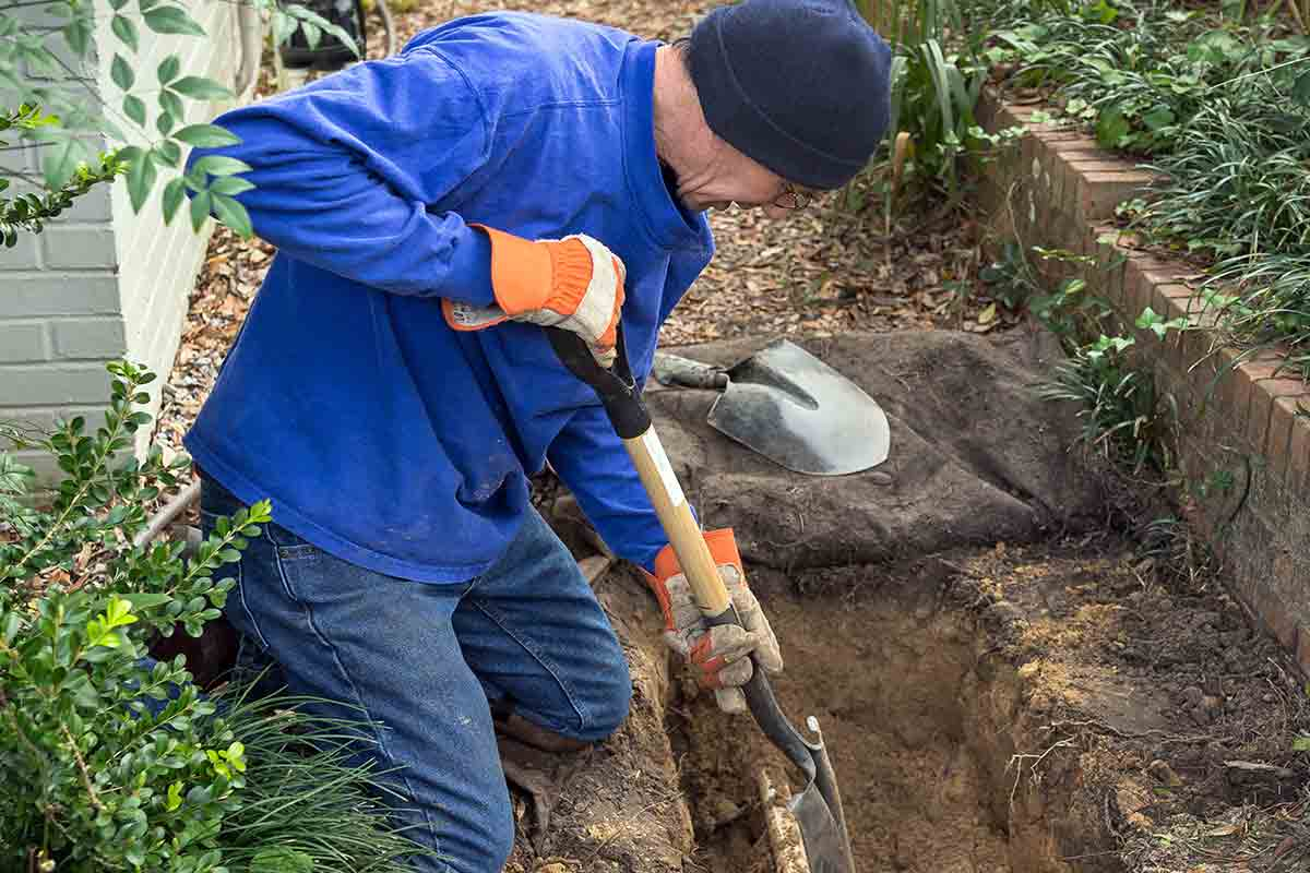 man digging trench to replace old sprinkler line