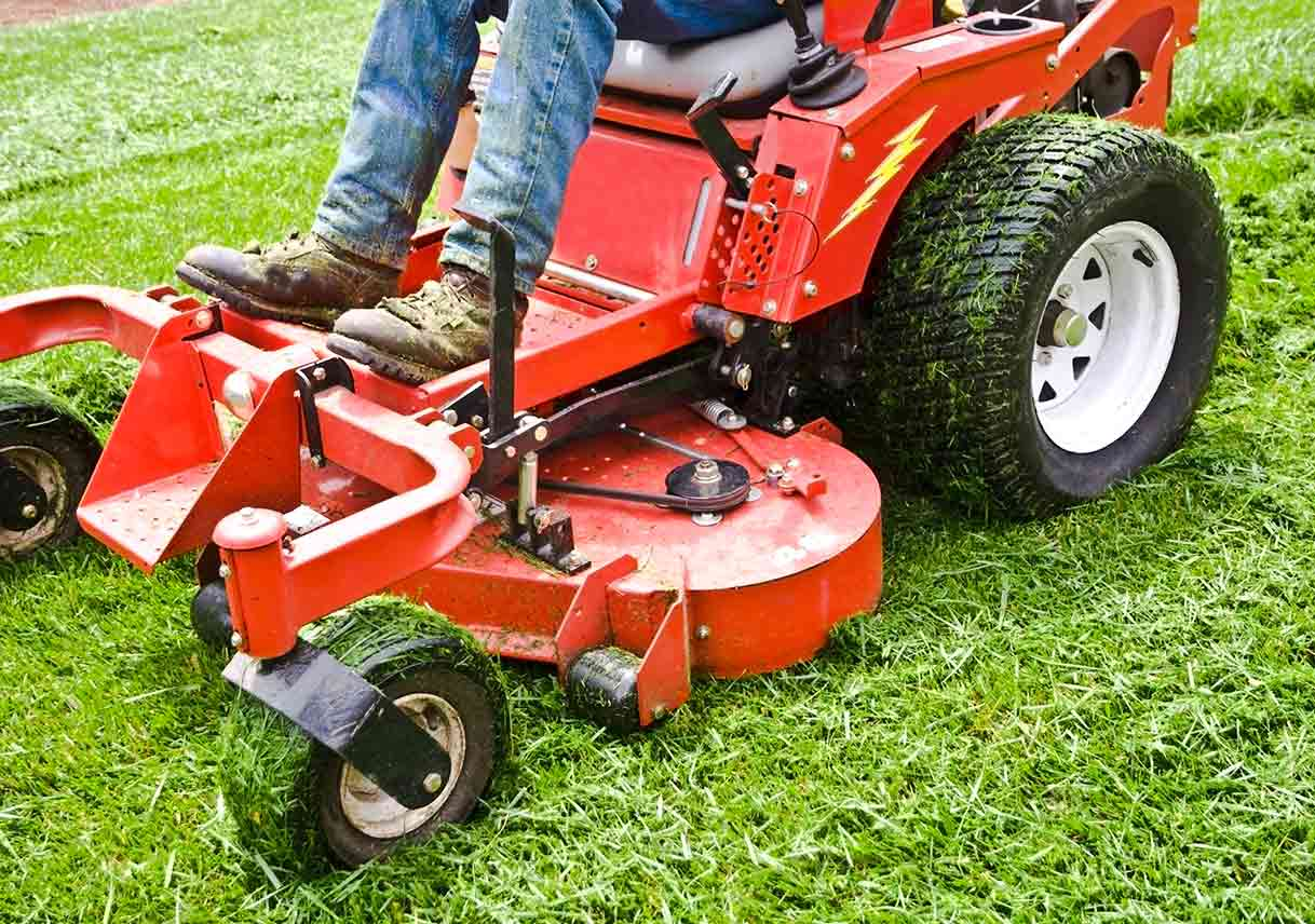 Man riding lawn mower with grass on tires