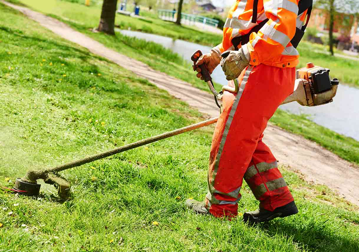 professional lawn mower worker cutting green grass