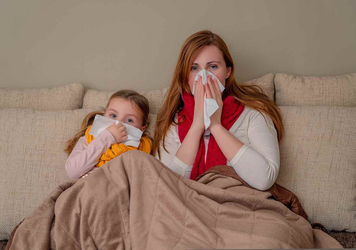 mom and daughter with flu on couch